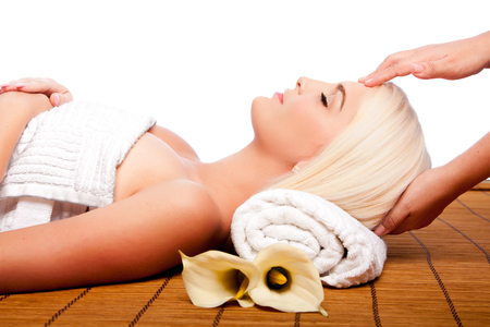 Beautiful young woman relaxing at spa getting therapeutic pampering forehead massage. Imagens
