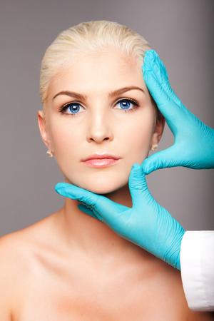 Bel volto di giovane donna per l'estetica del viso concetto di cura della pelle toccata dalla cosmetica estetista chirurgo plastico. Archivio Fotografico - 64537049