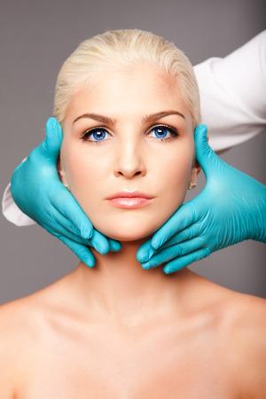 Bel volto di giovane donna per l'estetica del viso concetto di cura della pelle toccata dalla cosmetica estetista chirurgo plastico. Archivio Fotografico - 64537142