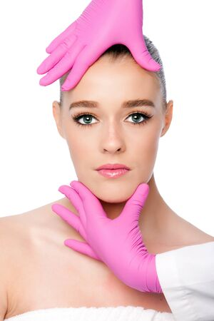 Beautiful face ready for Cosmetic skincare spa beauty treatment with pink gloves, on white.
