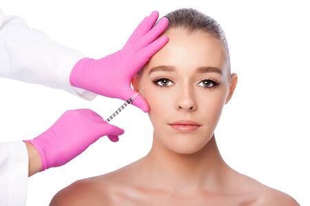 Beautiful face crows feet injection Cosmetic skincare spa beauty treatment with pink gloves by eye, on white.