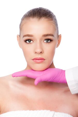 Beautiful face ready for Cosmetic skincare spa beauty treatment with pink glove, on white. Imagens