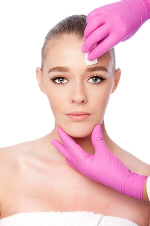 Beautiful face cleansing Cosmetic skincare spa beauty treatment with pink gloves and sponge, on white.