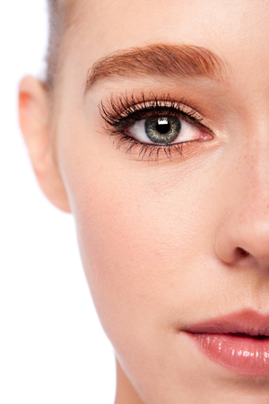 woman eye: Beautiful eye with eyebrow and lashes on half face of attractive young woman. Stock Photo