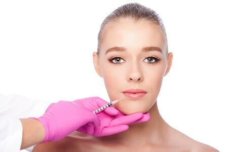filler: Beautiful face lip filler collagen injection Cosmetic spa beauty treatment with pink gloves, on white.