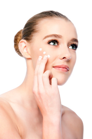 Beautiful woman applying Moisturizing facial skincare treatment cream.
