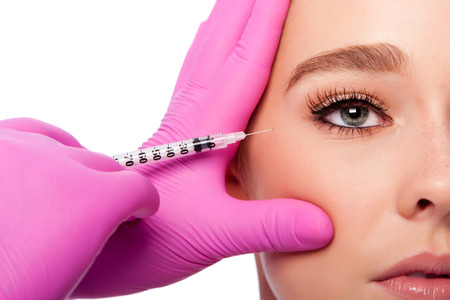 Beautiful face crows feet collagen filler injection Cosmetic skincare spa beauty treatment with pink gloves by eye, on white. Reklamní fotografie