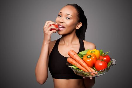 Beautiful healthy happy black asian woman eating delicious vegetables. Imagens