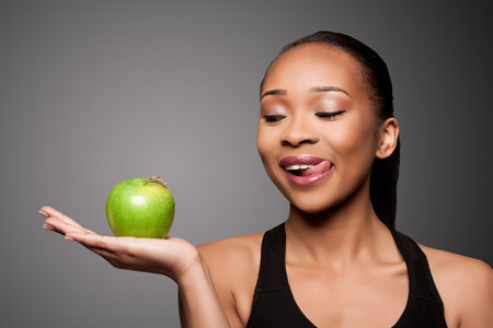 Beautiful healthy happy licking black asian woman with delicious apple in hand.