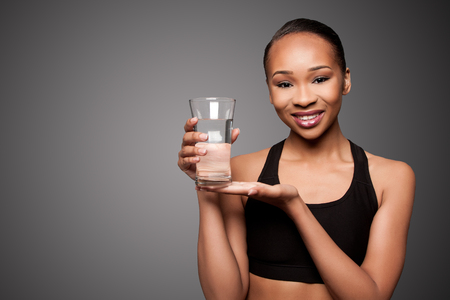 Beautiful happy smiling healthy black asian woman with glass of water, skincare concept. Imagens