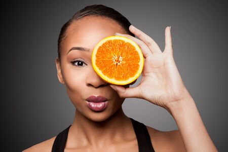 Beautiful healthy happy black asian woman holding delicious orange mandarin fruit in front of eye. Imagens