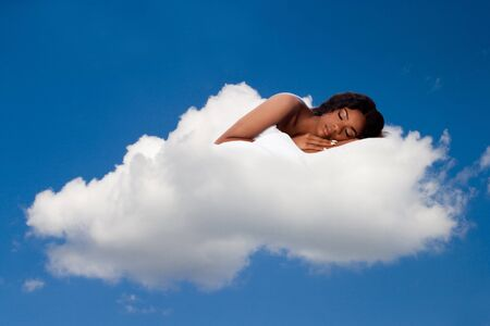 on cloud nine: Beautiful woman deeply asleep and dreaming on comfortable soft fluffy white cloud nine, concept. Stock Photo