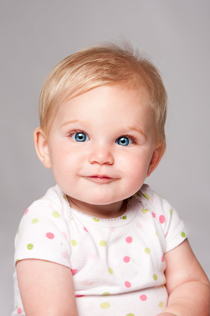 Adorable cute happy blue eyed baby infant face with blond hair.