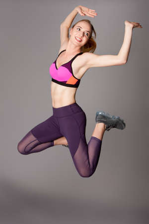Happy beautiful woman doing healthy fitness workout power jump.