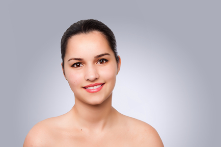 Beauty portrait face of happy smiling beautiful brunette woman with brown eyes and smooth skin, aesthetics cosmetics skincare concept. Imagens