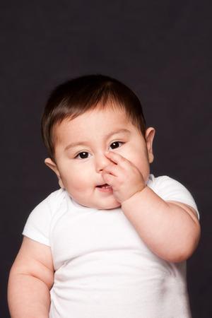 Carino divertente dentizione faccia del bambino espressione succhiare il dito pollice in bocca mentre indossa tutina bianca, su grigio.