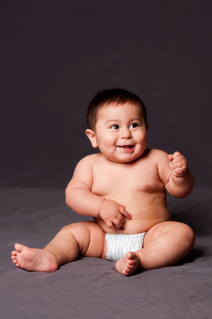 Cute happy funny smiling baby sitting while wearing diaper, on gray.