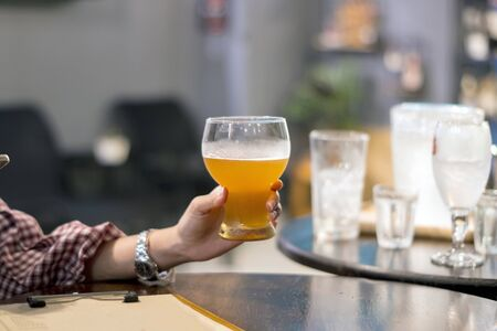 Hands holding Beer glasses clinking in bar or pub on table with food