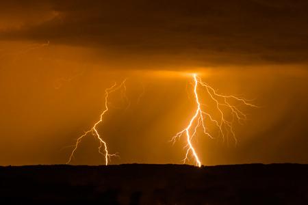 rayo electrico: Doble rayo durante la tormenta en el cielo rojo Foto de archivo