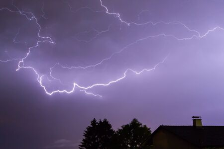 lightnings: Lightnings over a house and a tree in the night with blue sky