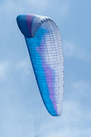 blue open parachute flying in blue sky