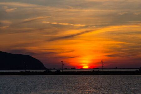natural sunset at lefkas lagoon in greece with dike and water, streetlamps