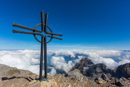summit cross of Uri Rotstock mountain in Swiss alps, blue sky, sea of fog