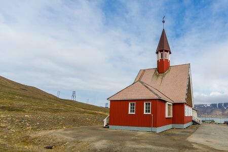 red Svalbard church in Longyearbyen, cloudy blue sky, sunshine