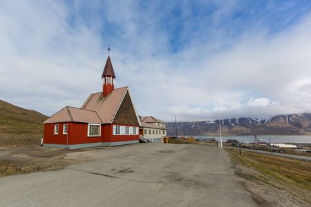 red Svalbard church in Longyearbyen, street, cloudy blue sky, mountains