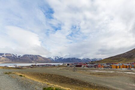 city of Longyearbyen, Svalbard, cloudy blue sky, snowcapped mountains