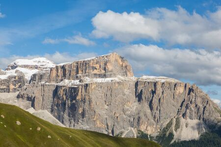 snow-capped Piz Boe mountain of Sella group in  Dolomites, cloudy blue sky