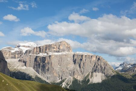 snow-capped Sella group in  Dolomites, cloudy blue sky