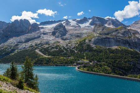 lake Fedaia and Marmolada mountain in italian dolomites, cloudy blue sky