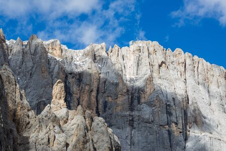 south face of snowcapped Marmolada mountain, cloudy blue sky
