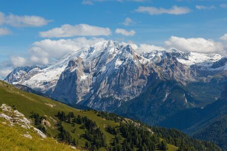 Marmolada Dolomite mountains in summer, green meadow, blue sky Imagens - 131398618