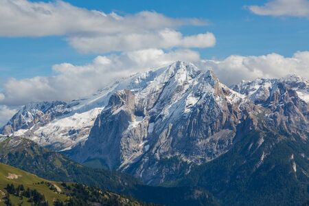 snow-capped Marmolada mountain summit in summer, cloudy blue sky Imagens - 131398619