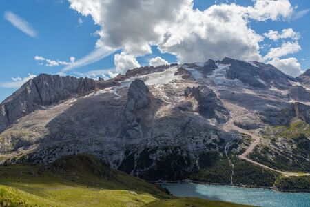 UNESCO world heritage Marmolada glacier in summer and lake Fedaia in italian dolomites Imagens - 131398623