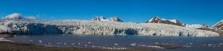 detailed panorama view on Esmarkbreen glacier ice front in Svalbard, blue sky