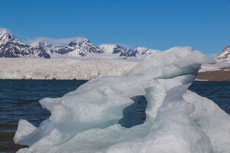 floating piece of ice in front  of Esmarkbreen glacier in Svalbard, blue sky