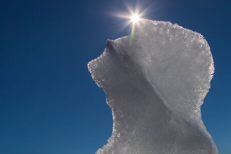 melting ice floe with sun and sunbeams and blue sky