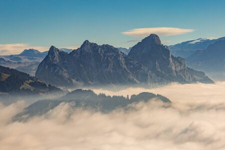 natural sea of fog and Swiss Mythen mountains in evening sun Imagens