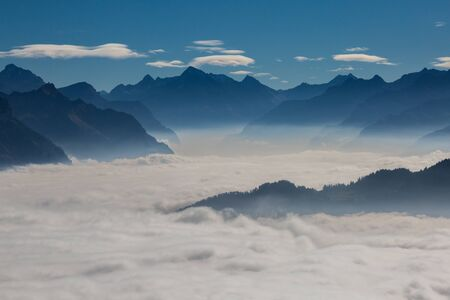 natural sea of fog over Schwyz and Uri in Swiss mountains with blue sky