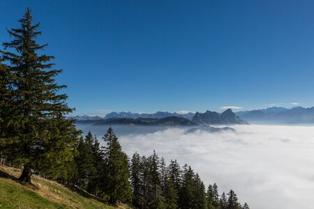 Swiss Mythen mountains and blue sky above natural sea of fog