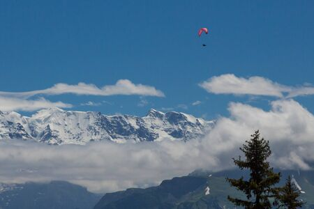paragliding in Swiss alps in Bernese highlands, snowcapped mountains, blue sky
