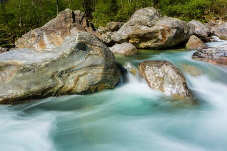 natural green Verzasca river water with stones in shunshine