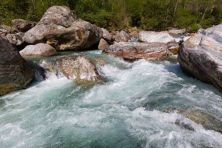 natural wild water of Verzasca river in Ticino in Switzerland with stones in shunshine