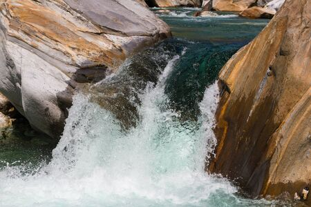 wild natural cascade of Verzasca river in Ticino Switzerland in shunshine