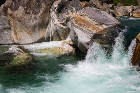 natural wild water of Verzasca river in Ticino in Switzerland with cascade in shunshine