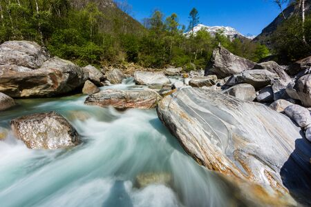 colorful Verzasca river in Ticino in Switzerland in spring, blue sky, sunshine