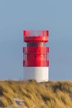 red lighthouse on Helgoland Duene island in blue sky and golden grassland